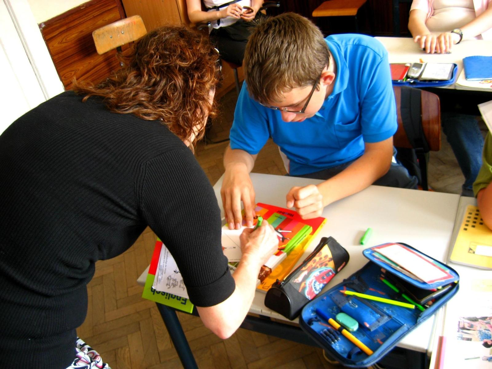 Projects Abroad volunteer helps a student with his classwork during her Childcare Project in Romania